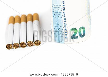 Euro banknotes wrapped rolled up winded with cigarettes on the white table. Concept of the prices cost of cigarettes tabacco