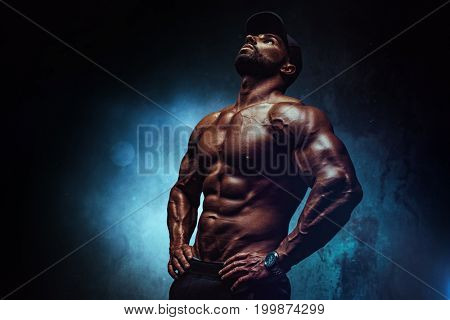 Young strong man bodybuilder in cap on wall background. Dark dramatic colors.