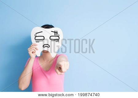 woman take confuse tooth and show something on the blue background