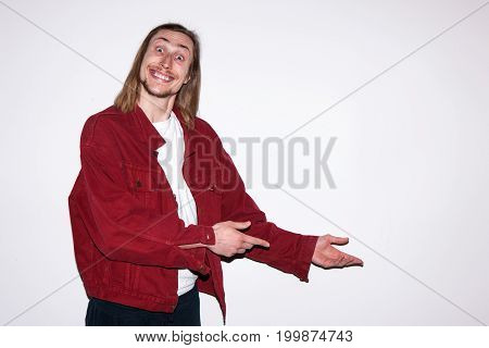 Happy european casual adult man on background with free space. Young male pointing at copy space, commercial white backdrop, advertising concept