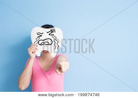 woman take cry tooth and show something on the blue background