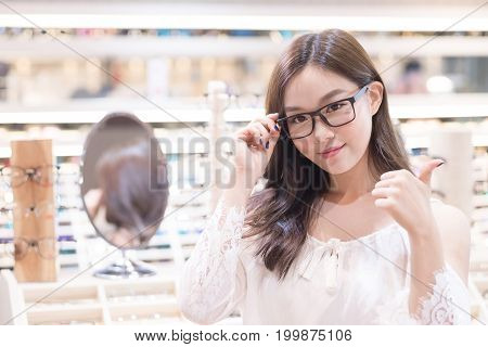 beauty woman wear eyeglasses and show thumb up in the store