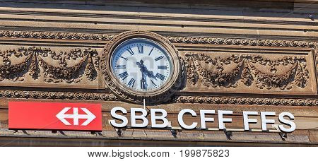 Zurich, Switzerland - 20 July, 2016: a clock and the sign of the Swiss Federal Railways on the facade of the Zurich Main railway station. Zurich Main railway station building was designed by architect Jakob Friedrich Wanner and opened in 1871.