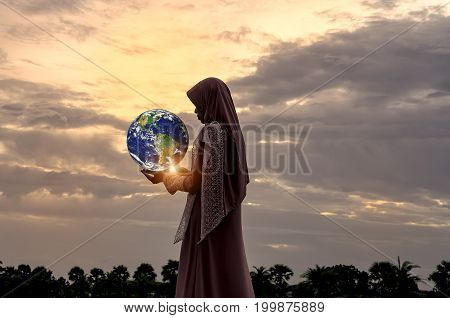Veiled Islamic woman wearing a burka standing in a beam of overhead light in atmospheric darkness in a spiritual portrait.Elements of this image furnished by NASA.
