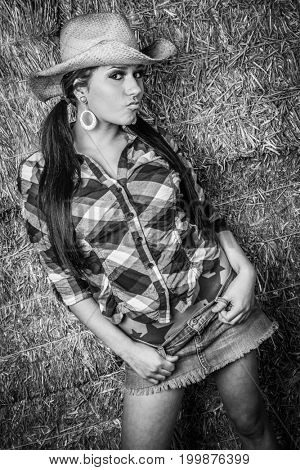 Beautiful country cowgirl in hay