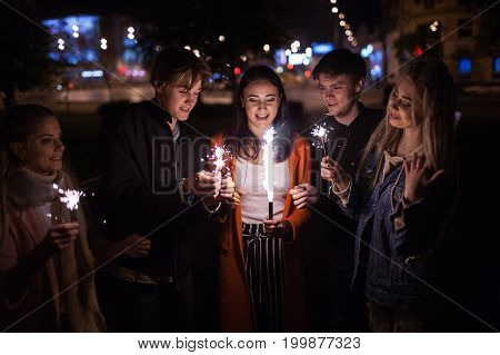 Friends happy celebration with sparklers outdoors. Young people christmas party. New Year concept