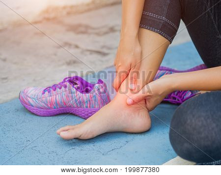Young woman massaging her painful ankle. from exercising and running. Sport and excercise concept.