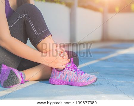 Young woman suffering from an ankle injury while exercising and running. Sport excercise concept.