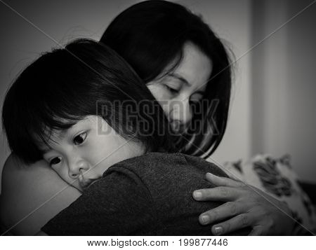 Black and white of sad little boy being hugged by his mother at home. Parenthood Love and togetherness concept.