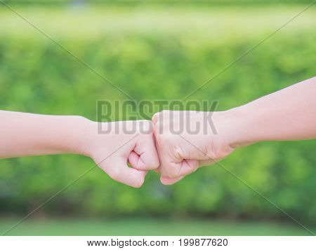 Closeup mother and son are fist bumping in green background. People charity and family concept.