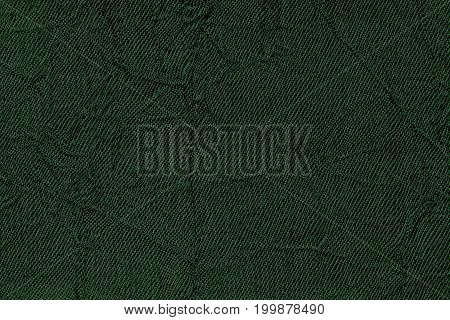 Dark green wavy background from a textile material. Fabric with fold texture closeup. Creased shiny emerald cloth.