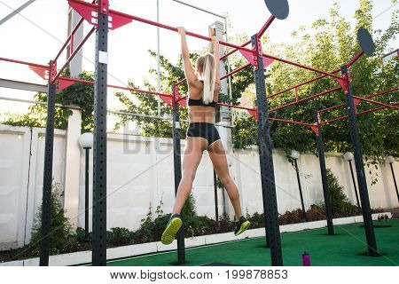Just being herself.Training body to perfection. Full length rear view of young woman in sports uniform hanging while exercising outdoors. Suspension training.