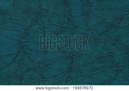 Dark blue wavy background from a textile material. Fabric with fold texture closeup. Creased shiny turquoise cloth.