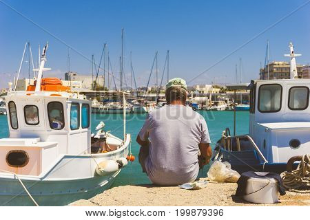 Heraklion - In Greece, Crete in 2017.  View on an old seated Fisherman with casual clothes and white Ships at the Harbor of Heraklion. Close-up of an old relaxed Fisherman in Summer.