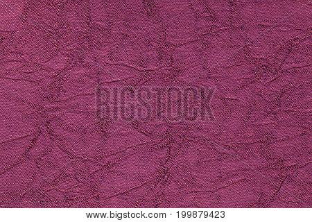 Dark purple wavy background from a textile material. Fabric with fold texture closeup. Creased shiny magenta cloth.