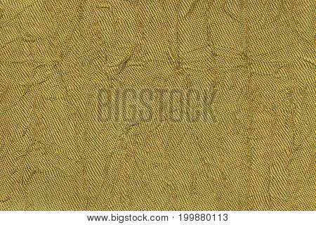 Dark yellow wavy background from a textile material. Fabric with fold texture closeup. Creased shiny golden cloth.