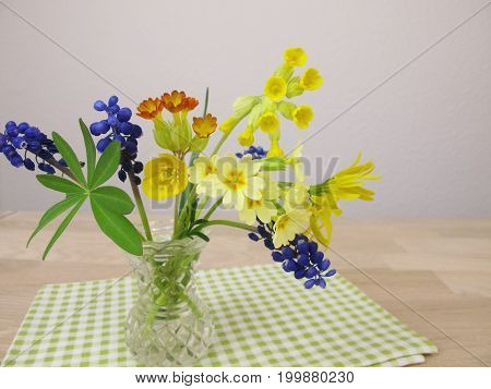 Small spring bouquet in vase on table