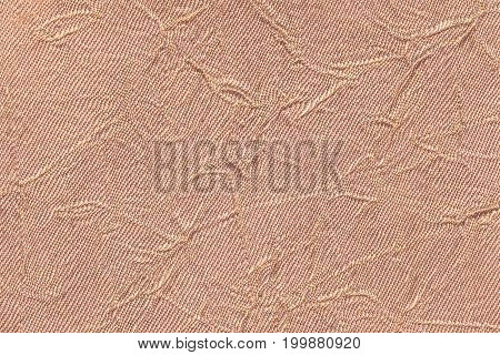 Light brown wavy background from a textile material. Fabric with fold texture closeup. Creased shiny beige cloth.