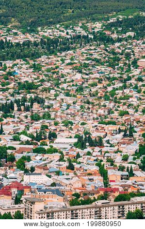 Tbilisi, Georgia. Aerial View Of Populated Residential Area. Buildings With Red And White Roofs Interspersed With Green Trees In Sunny Summer Day.