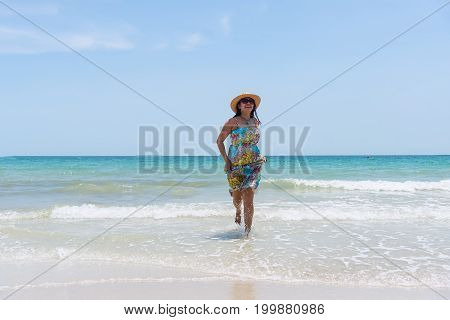 Freedom lifestyle and holiday concept. Happy woman jumping on the beach against beautiful yellow sunset.