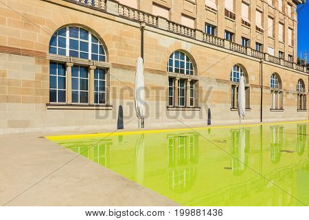 Zurich, Switzerland, 20 July, 2016: partial view of the facade of the main building of the University of Zurich and a water pool in front of it. The University of Zurich in the city of Zurich is the largest university in Switzerland, founded in 1833.