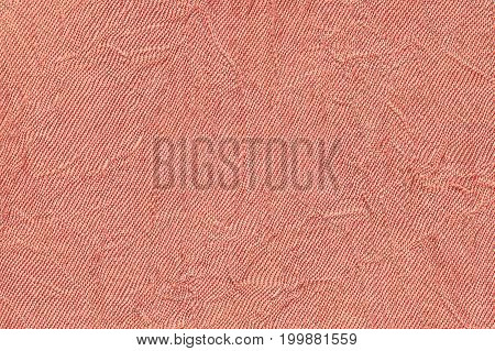 Light red wavy background from a textile material. Fabric with fold texture closeup. Creased shiny coral cloth.