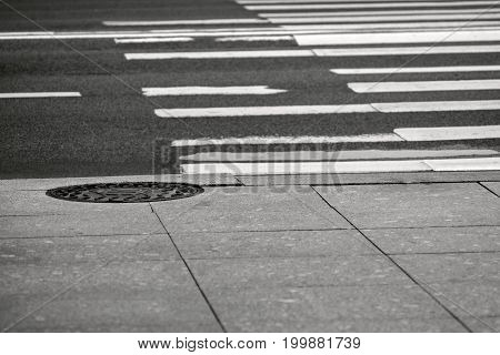 empty part of the highway with the crosswalk and the sidewalk with the manhole in the photo of monochrome