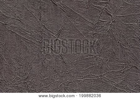 Dark gray wavy background from a textile material. Fabric with fold texture closeup. Creased shiny brown cloth.