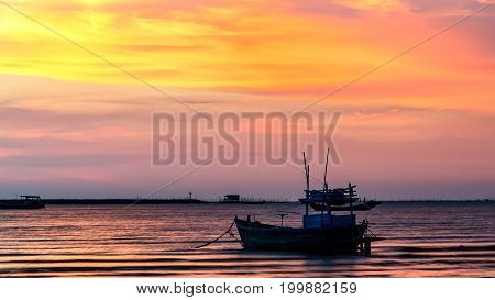 small fishing boat at beach with sunset