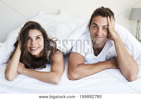 Good looking couple lying under duvet smiling