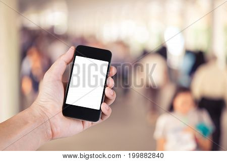 Person Using Smartphone White Screen Holder On Hand With  Many People Walking On Skywalk In The Big