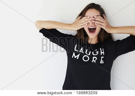 Young Surprised brunette covering eyes in studio