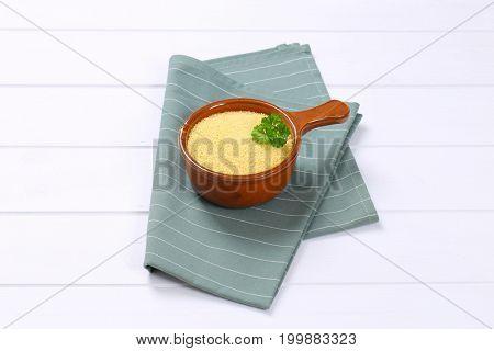 saucepan of raw couscous on grey place mat