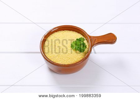saucepan of raw couscous on white wooden background