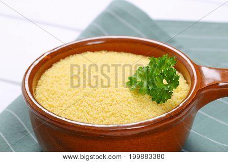 saucepan of raw couscous on grey place mat - close up