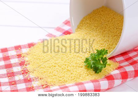 bowl of raw couscous split out on checkered place mat - close up