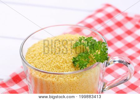 cup of raw couscous on checkered place mat - close up