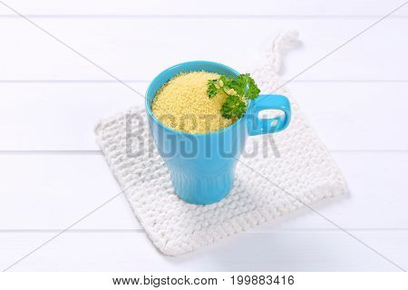 cup of raw couscous on white table mat