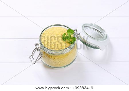 jar of raw couscous on white wooden background