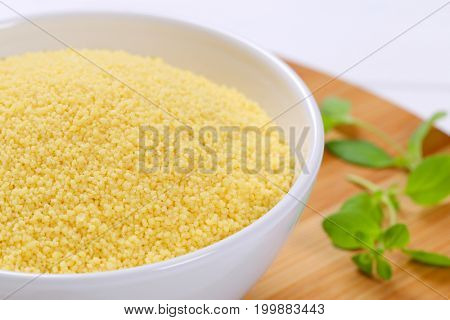 bowl of raw couscous on wooden cutting board - close up