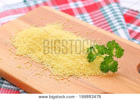 pile of raw couscous on wooden cutting board - close up