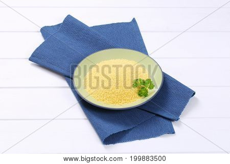 plate of raw couscous on blue place mat