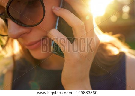 Beauty woman in sunglasses talking on the smartphone while walking down the street at sunset close up
