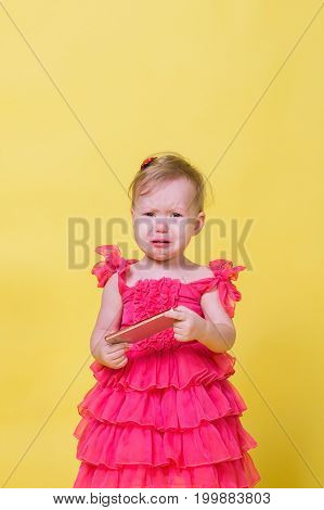 Girl toddler in a pink dress on a yellow background holding a smartphone and crying.