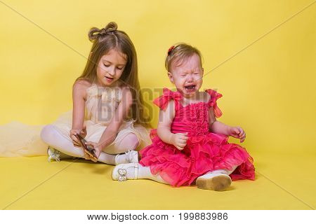 The younger sister cries, the elder keeps the phone on yellow background.