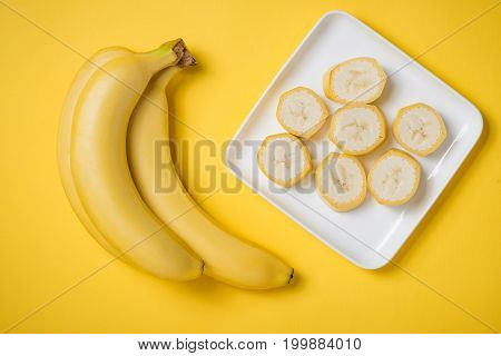 A Banch Of Bananas And A Sliced Banana In A Dish Over Yellow Background.