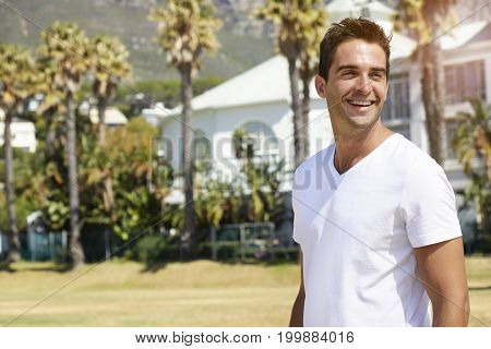 Handsome White t-shirt guy smiling in park
