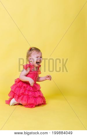 Little girl in pink dress kneeling and crying on a yellow background.