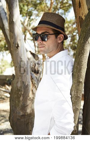 Sunglasses and hat guy leaning against tree content