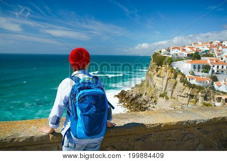 Woman in red hat with a backpack enjoys a view of the ocean coast near Azenhas do Mar Portugal